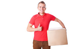 Smiling delivery man is holding a paper box and making the ok ge Royalty Free Stock Image