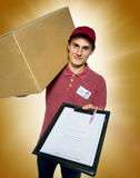 Smiling delivery man holding a paper box Royalty Free Stock Images
