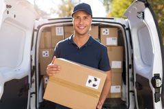 Smiling delivery man loading boxes into his truck stock photography
