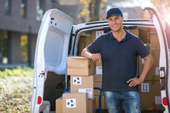 Smiling delivery man loading boxes into his truck royalty free stock photos