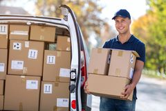 Smiling delivery man loading boxes into his truck stock image
