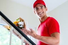 Delivery man holding flower bouquet. Smiling delivery man in red cap and t-shirt holding flower bouquet stock image
