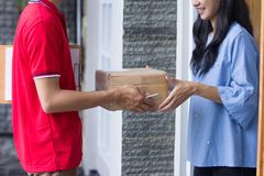 Delivery man delivering box. Smiling delivery man in red uniform delivering parcel box to recipient Stock Image