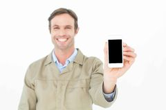 Smiling delivery man showing smart phone Royalty Free Stock Photo
