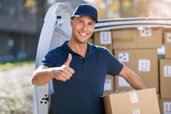 Smiling delivery man loading boxes into his truck stock photos