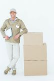 Smiling delivery man standing by stack of boxes Royalty Free Stock Images