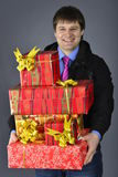 Smiling delivery man. In uniform carrying packages Royalty Free Stock Photos