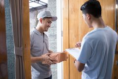 Delivery man delivering box. Smiling delivery men holding a cardboard box while handsome men putting signature in clipboard Royalty Free Stock Image