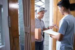 Delivery man delivering box. Smiling delivery men holding a cardboard box while handsome men putting signature in clipboard Royalty Free Stock Photos