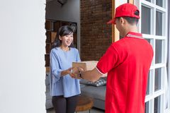 Delivery man delivering box. Smiling delivery men in red uniform delivering parcel box to recipient Stock Photo