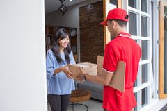 Delivery man delivering box. Smiling delivery men in red uniform delivering parcel box to recipient Royalty Free Stock Images