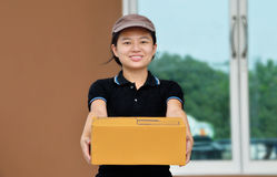 Smiling delivery woman, holding  carton box Royalty Free Stock Images