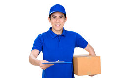 Smiling deliveryman holding box and giving clipboard Royalty Free Stock Images