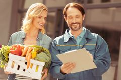 Smiling deliveryman standing near his client. Little business. Cheerful female person expressing positivity and keeping package with organic products while royalty free stock photography