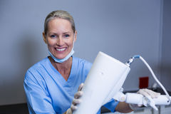 Smiling dental assistant adjusting light in clinic. Portrait of smiling dental assistant adjusting light in clinic Stock Photography