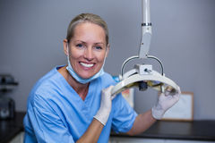 Smiling dental assistant adjusting light in clinic. Portrait of smiling dental assistant adjusting light in clinic Royalty Free Stock Images