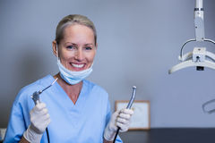 Smiling dental assistant holding dental tools in clinic Stock Photography