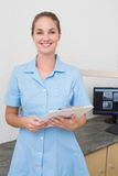 Smiling dental assistant looking at camera holding clipboard Royalty Free Stock Image
