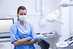 Smiling dental assistant standing with arms crossed. Portrait of smiling dental assistant standing with arms crossed in dental clinic Stock Image
