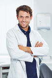 Smiling dentist with arms crossed. Smiling dentist with his arms crossed in his dental practice Royalty Free Stock Photo