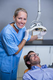 Smiling dentist assistant adjusting light over patients mouth Royalty Free Stock Image