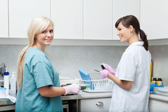 Smiling Dentist With Assistant Cleaning Medical. Portrait of smiling female dentist with assistant cleaning medical instruments at clinic Stock Photos