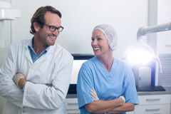 Smiling dentist and dental assistant standing with arms crossed Stock Image