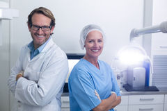 Smiling dentist and dental assistant standing with arms crossed Royalty Free Stock Photos