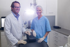 Smiling dentist and dental assistant standing together in dental clinic Royalty Free Stock Photography