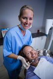 Smiling dentist examining a young patient with tools Stock Photos