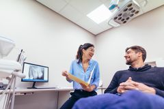 Smiling dentist and patient at dental clinic. Happy dentist and patient at dental clinic. Smiling doctor and patient discussing report at dental clinic Stock Photo