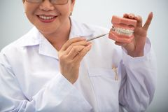 Smiling dentist showing innovative teeth braces royalty free stock photo