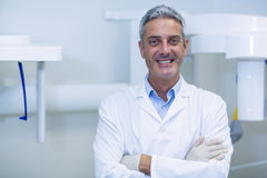 Smiling dentist standing in dental clinic Royalty Free Stock Photography