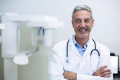 Smiling dentist standing in dental clinic Stock Photos