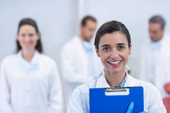 Smiling dentist standing at dental clinic. Portrait of smiling dentist standing at dental clinic Stock Image