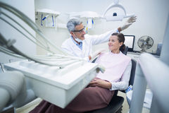 Smiling dentist talking to patient Royalty Free Stock Images