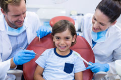 Smiling dentists examining young patient Stock Photos