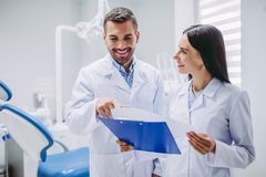 Dentists looking at clipboard. Smiling dentists looking at clipboard in modern dental clinic stock photos