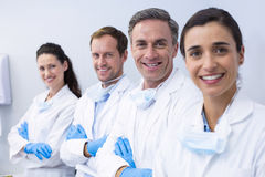 Smiling dentists standing with arms crossed. Portrait of smiling dentists standing with arms crossed in dental clinic Royalty Free Stock Photo
