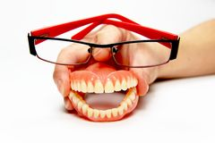 Smiling denture with glasses. The total denture upper and lower held in the hand Royalty Free Stock Image