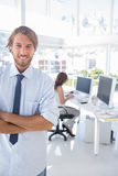 Smiling desginer standing in office with arms crossed Stock Photography