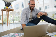 Smiling designer holding disposable cup using laptop. While sitting on floor Stock Photos