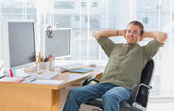 Smiling designer leaning back at his desk Stock Images