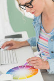 Smiling designer working at her desk using a colour wheel Stock Photo