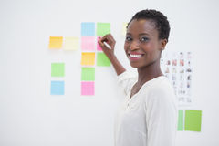 Smiling designer writing on sticky notes and looking at camera Stock Photography