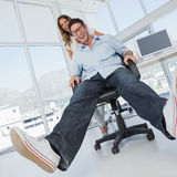 Smiling designers having fun with on a swivel chair Stock Photos