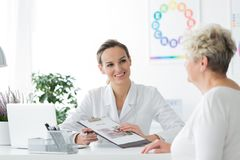 Smiling dietician with her patient. A smiling dietician sitting with her patient and showing her a diet plan stock photo
