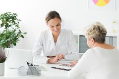 Dietician and patient during meeting. Smiling dietician and patient with nutritional problems preparing a diet plan during a meeting stock image