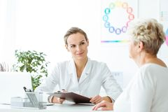 Smiling dietician taking medical history. Smiling dietician taking patient`s medical history during a visit at the office Royalty Free Stock Photos