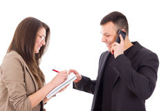 Smiling director on the phone and his secretary writing down not Royalty Free Stock Photos